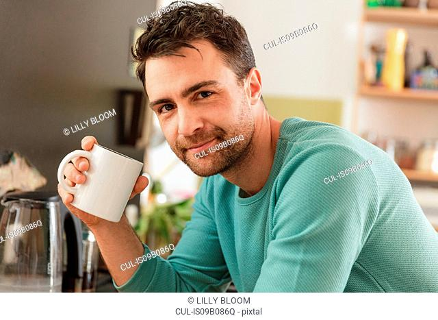 Portrait of man holding coffee cup looking at camera smiling