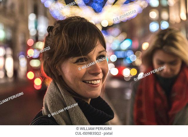 Young woman standing in illuminated street, smiling