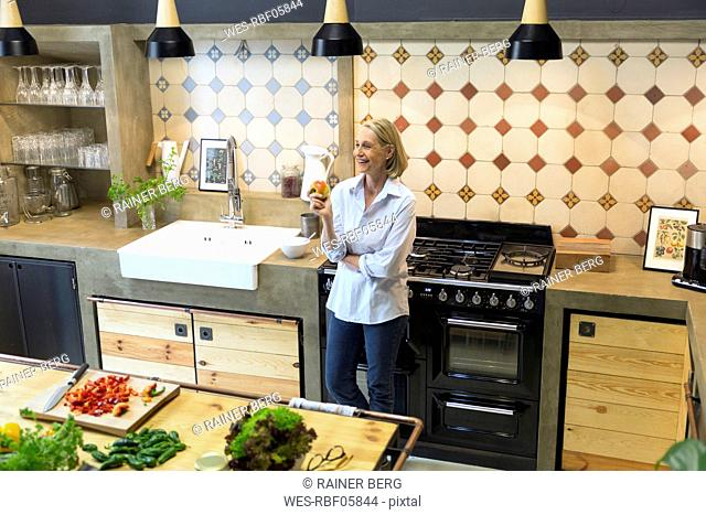 Smiling mature woman holding an apple in kitchen