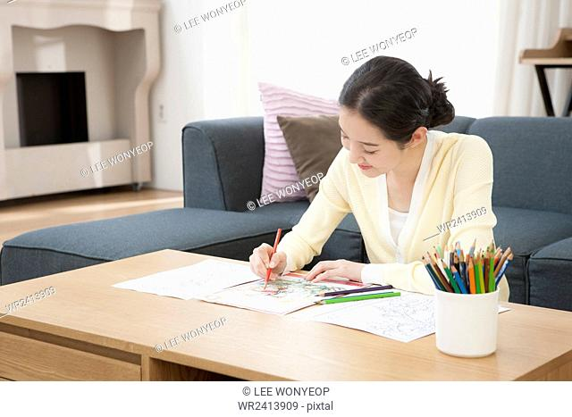 Portrait of young smiling woman drawing pictures with colored pencils