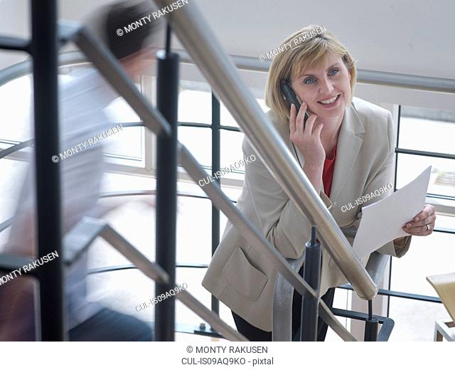 Businesswoman on phone in office stairwell