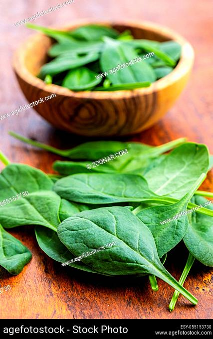 Baby spinach leaves. Green spinach on wooden table