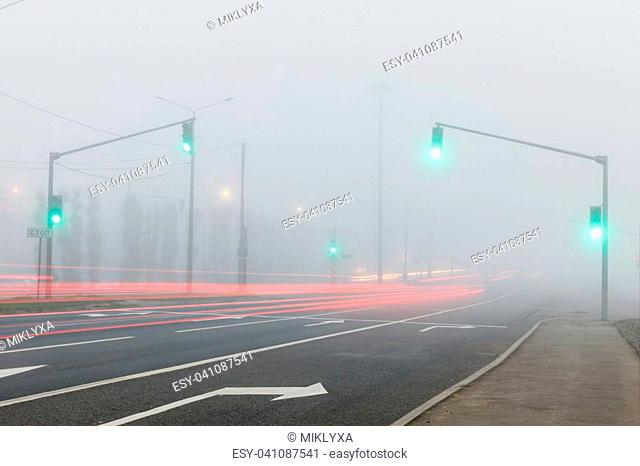 Freeway, traffic lights and tracks of car lights in fog at early morning