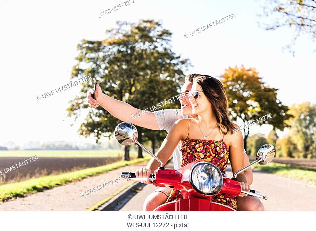 Happy young couple taking a selfie on motor scooter on country road