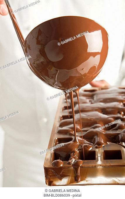 Baker pouring chocolate in mold