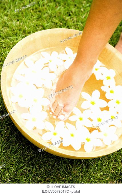 Hand in a bowl of floating frangipani flowers