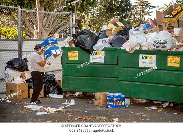 A Hispanic woman searches a dumpster for items of value in Santa Ana, CA