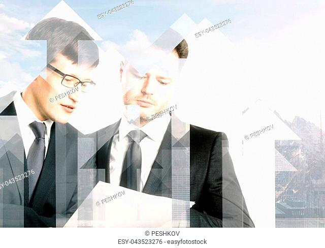 Handsome european businessmen disucssing contract together on abstract city background with arrows and sunlight. Partnership and investment concept