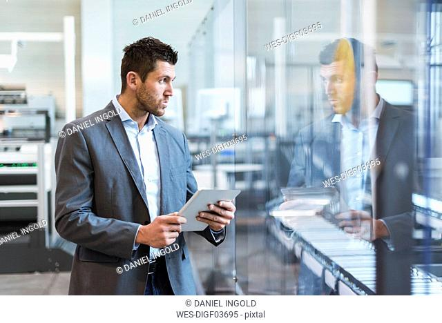 Businessman using tablet in modern factory