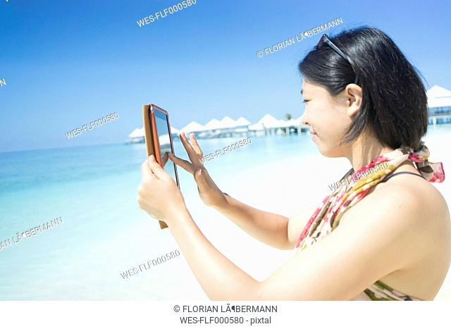 Maldives, Ari Atoll, young woman taking photograph with her mini tablet