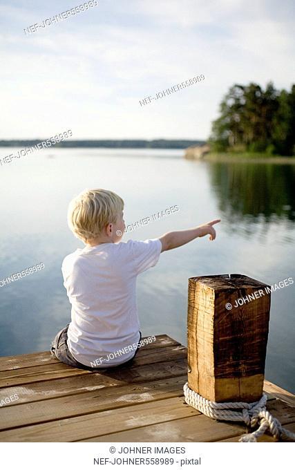 A boy sitting on a jetty, Sweden