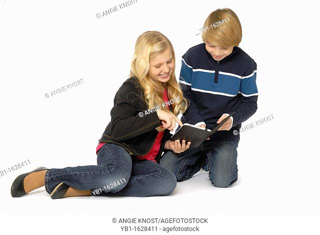Ten year old girl and eleven year old boy looking at a tablet computer