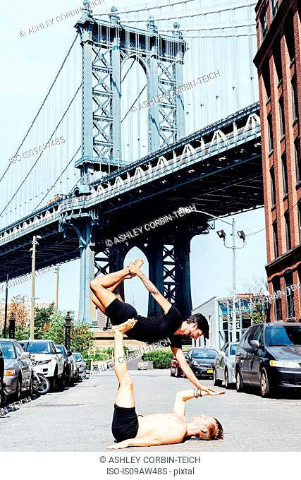 Man balancing on top of another in yoga position by Manhattan Bridge, New York, USA