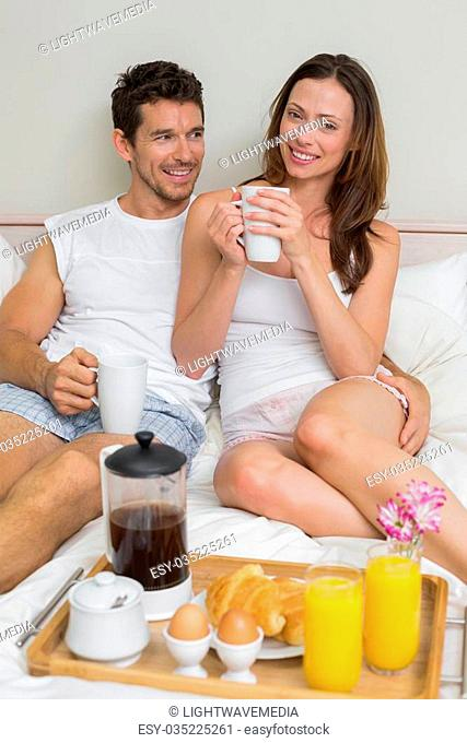 Happy young couple having breakfast in bed at home