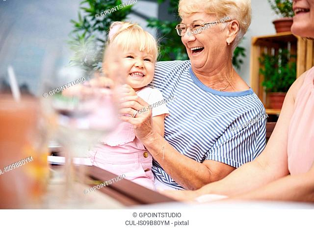Senior woman laughing with toddler granddaughter at family lunch on patio