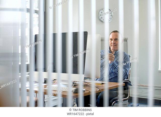 View through an office partition of a man seated at a desk