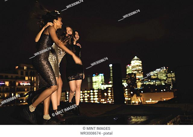 Group of young women standing on a rooftop celebrating