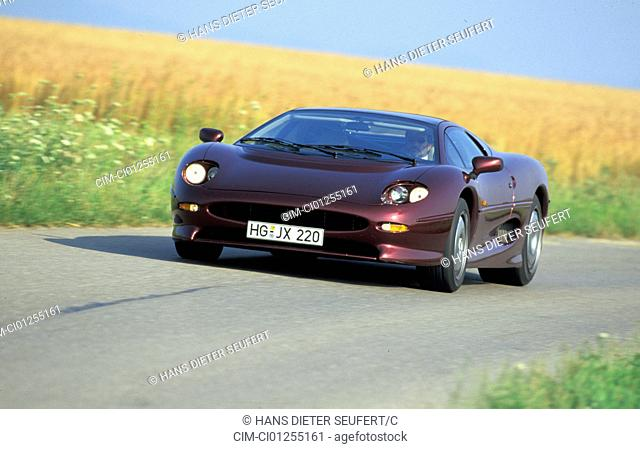Car, Jaguar XJ 220, model year 1994, wine-red-metallic, coupe/Coupe, roadster, driving, diagonal from the front, frontal view, country road