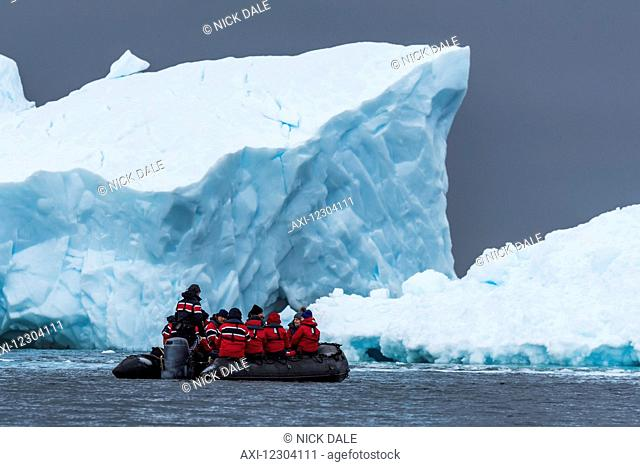 Black inflatable boat motoring past ice cliff; Antarctica
