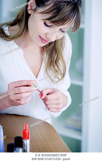 Woman applying polish on nails