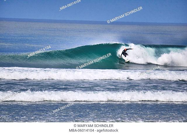 New Zealand, south island, surfer in wave, turquoise clear sea, blue sky