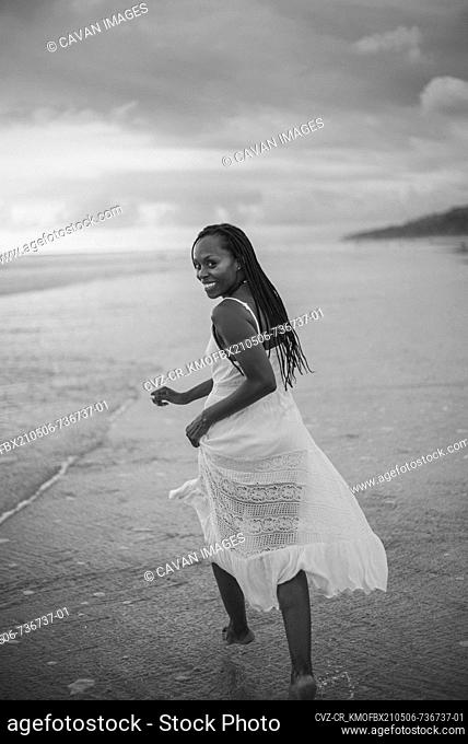a beauty black woman smile while she run in the beach