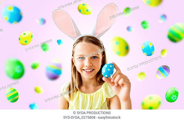 happy girl with colored easter egg over violet