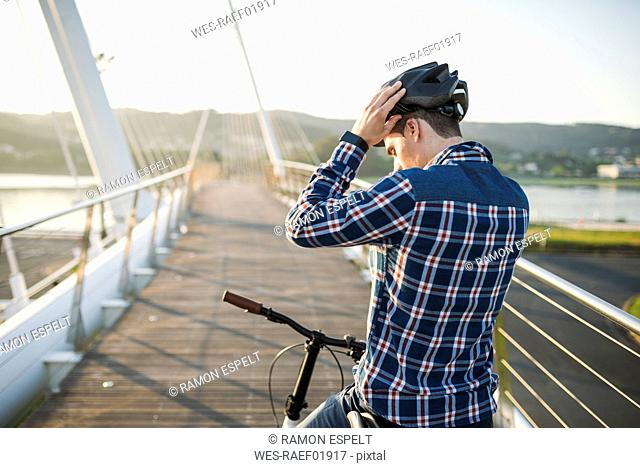 Young man on bicycle putting on helmet on a bridge