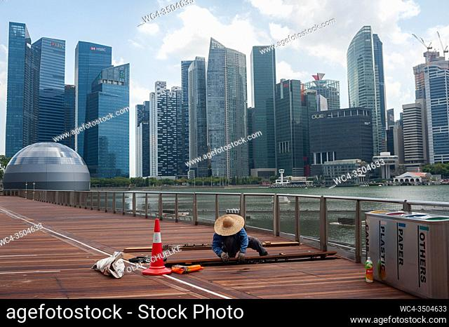 Singapore, Republic of Singapore, Asia - A worker repairs wooden planks along the waterfront in Marina Bay with the city skyline of the central business...