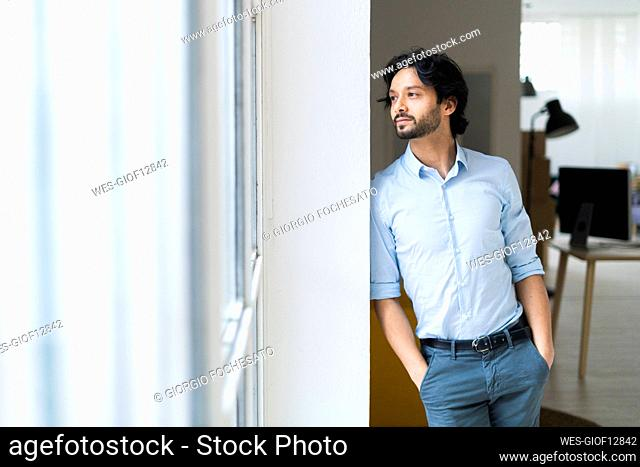 Thoughtful male entrepreneur with hands in pockets leaning on wall