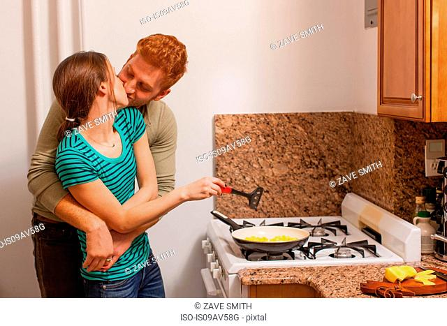 Young man in kitchen arms around young woman cooking on hob, kissing