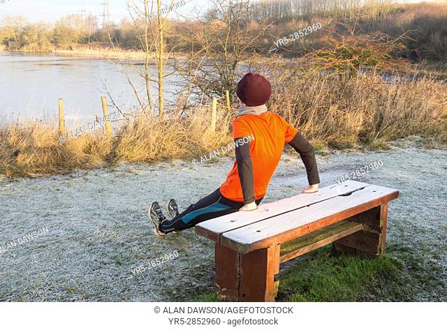 Billingham, north east England, UK. A mature male jogger warming up on a frost covered bench in Cowpen Woodland Park just after sunrise on a clear and frosty...
