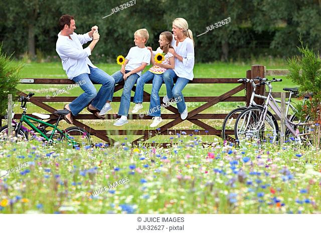 Man taking photograph of family on fence in wildflower field