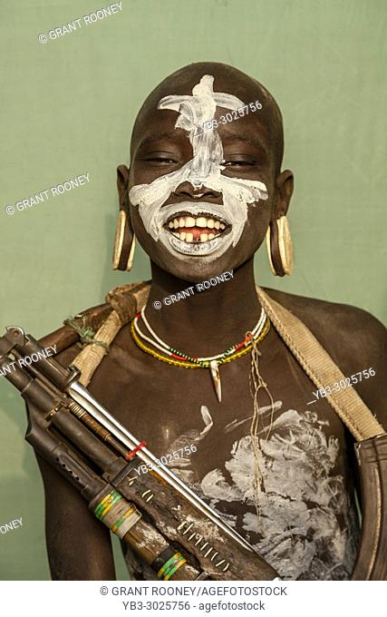 A Portrait Of A Boy From The Mursi Tribe Holding A Gun, Mursi Village, Omo Valley, Ethiopia