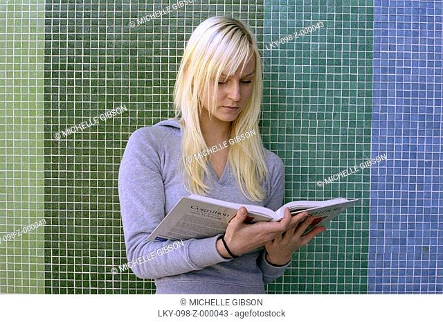 Portrait of student reading textbook