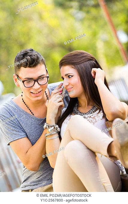 Girl and boy listen to cellphone talk together