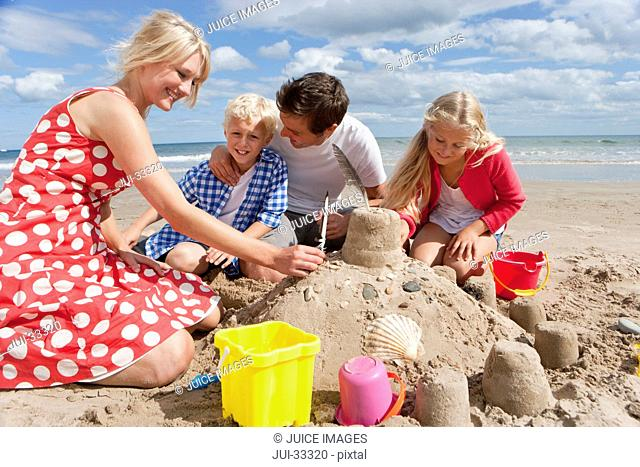 Family making sandcastle on sunny beach