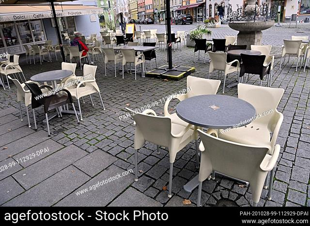 28 October 2020, Bavaria, Munich: A single guest sits in an otherwise empty street café in the pedestrian zone. Photo: Peter Kneffel/dpa