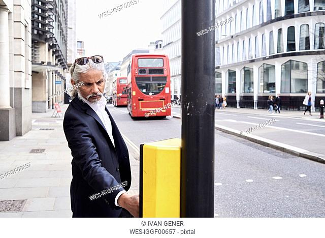 UK, London, bearded senior businessman pressing traffic lights button