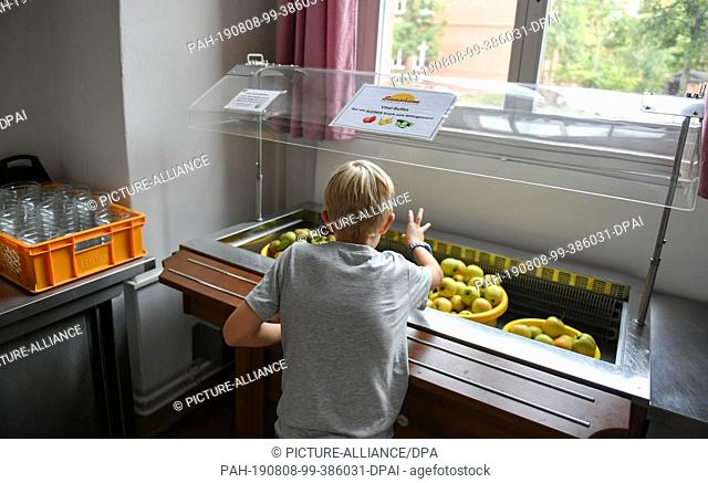 07 August 2019, Berlin: A pupil takes fruit provided for lunch in the canteen of the primary school at Wuhlheide. Photo: Jens Kalaene/dpa-Zentralbild/ZB
