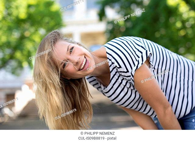 Portrait of woman bending forward looking at camera laughing