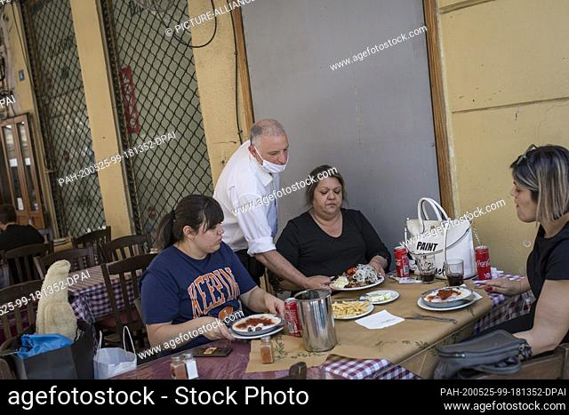 25 May 2020, Greece, Athen: A waiter with a face mask serves guests in a tavern in the Monastiraki district. Greece relaxes measures imposed because of the...