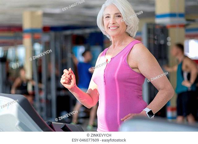 Happy running. Emotional pretty senior woman smiling and running on treadmill while training in a gym
