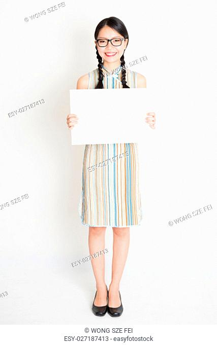 Portrait of young Asian woman in traditional qipao dress hand holding a white blank paper card, celebrating Chinese Lunar New Year or spring festival