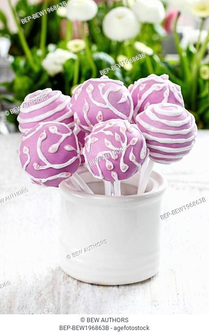 Lilac cake pops lavishly decorated with icing. Party dessert