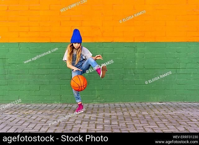 Young girl playing basketball, dribbling and lifting leg