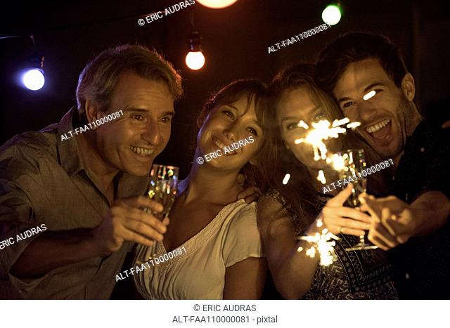 Friends celebrating with champagne and sparklers at party