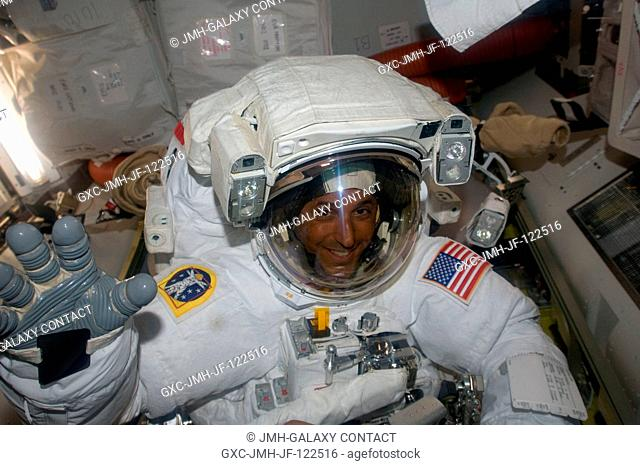Astronaut Joseph Acaba, STS-119 mission specialist, attired in his Extravehicular Mobility Unit (EMU) spacesuit, waves as he prepares to leave the Quest Airlock...