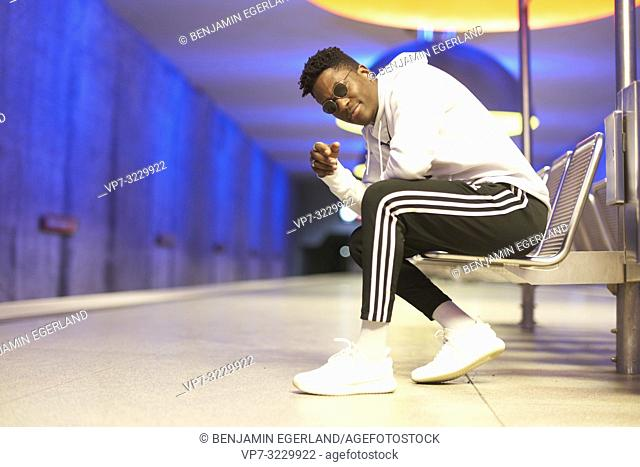 cool young man sitting on bench in underground station, public transport, in Munich, Germany