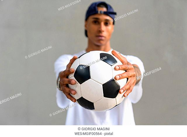 Young man's hands holding football, close-up